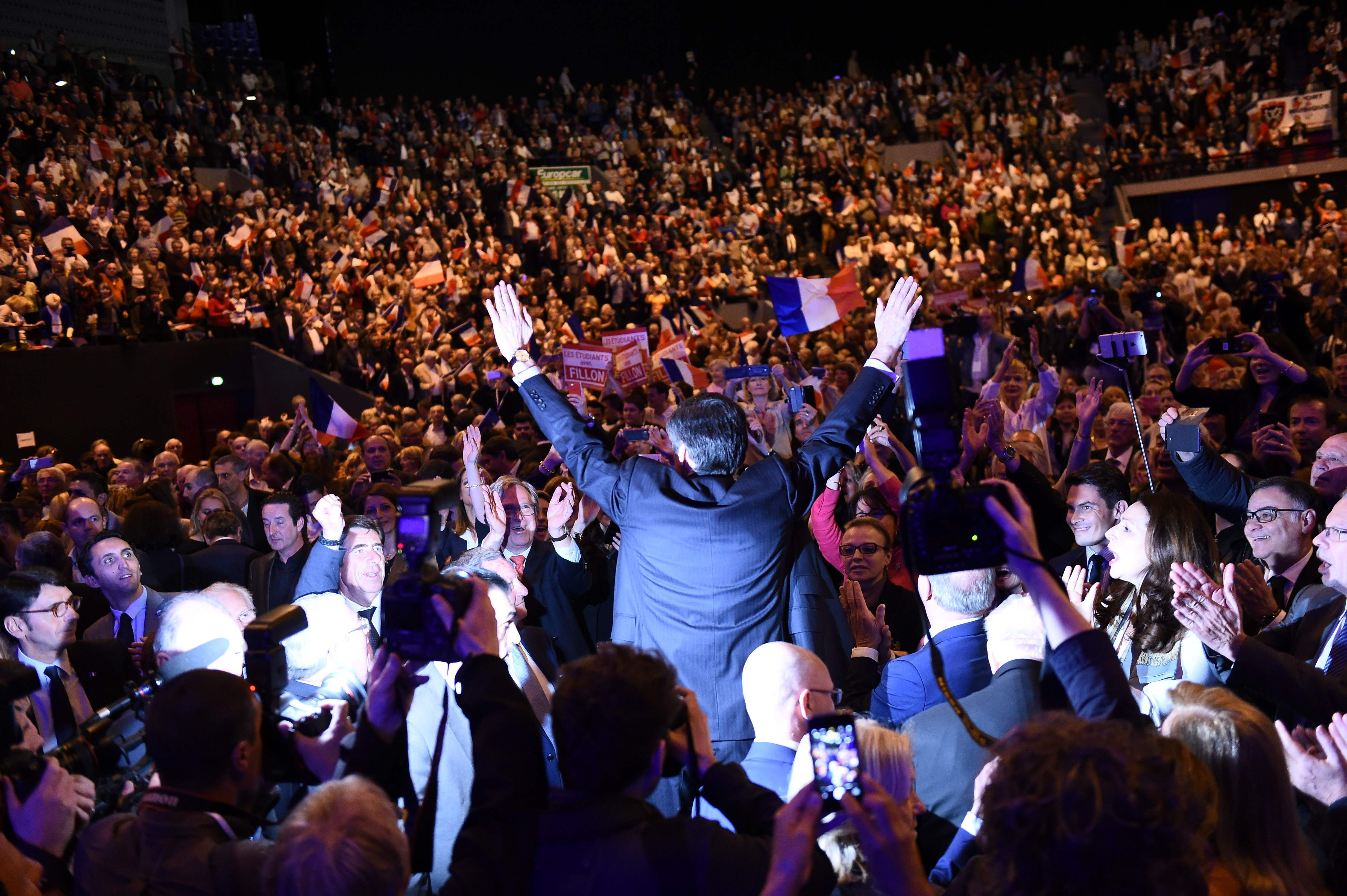 TOPSHOT - French presidential election candidate for the right-wing Les Republicains (LR) party Francois Fillon (back) gestures as he arrives to a campaign meeting on March 31, 2017, in Toulon, southern France. / AFP PHOTO / ANNE-CHRISTINE POUJOULAT / TT / kod 444