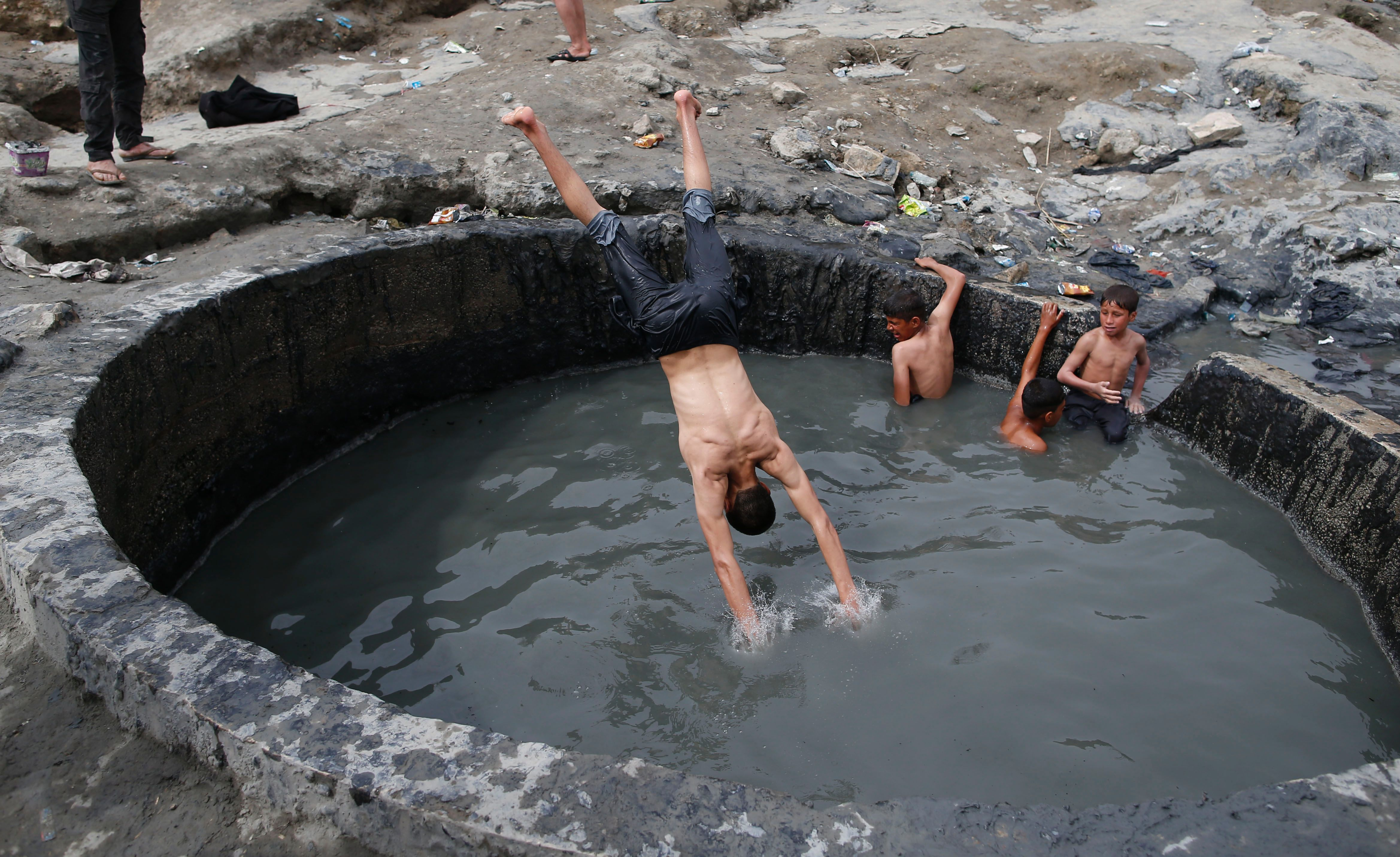 TOPSHOT - Iraqis bathe in a sulphur pond in the Hamam al-Alil area, about 14 kilometres from the southern outskirts of Mosul, on April 1, 2017. More than 200,000 people have fled west Mosul since the operation to oust the Islamic State group began last month, and officials and witnesses say that air strikes have taken a devastating toll on civilians who remained in the city. / AFP PHOTO / AHMAD GHARABLI / TT / kod 444