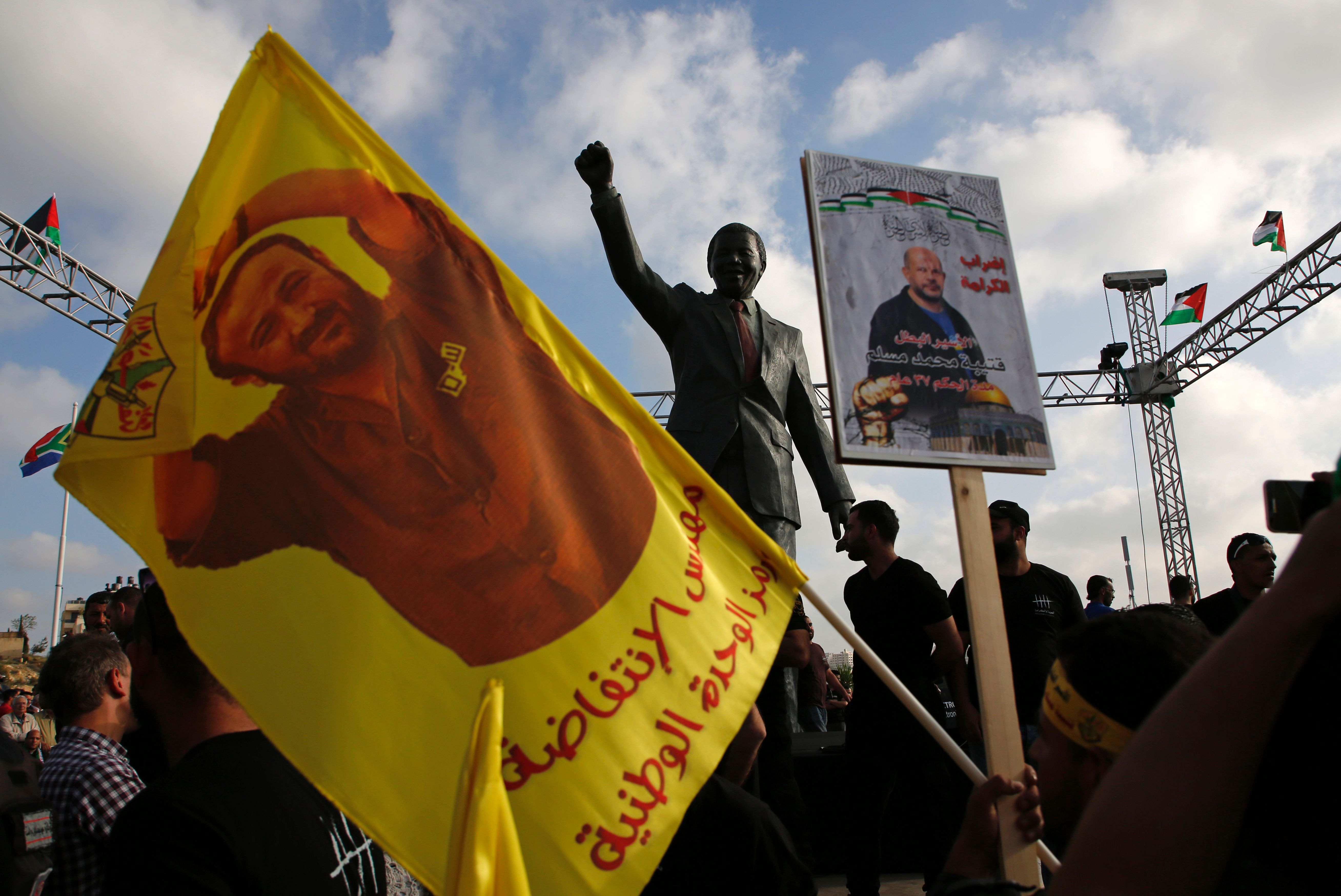 TOPSHOT - Protesters hold up portraits of Palestinian leader and prominent prisoner Marwan Barghouti in front of a statue of Nelson Mandela in the West Bank city of Ramallah on May 3, 2017, during a demonstration in support of Palestinian prisoners on hunger strike in Israeli jails. / AFP PHOTO / ABBAS MOMANI / TT / kod 444
