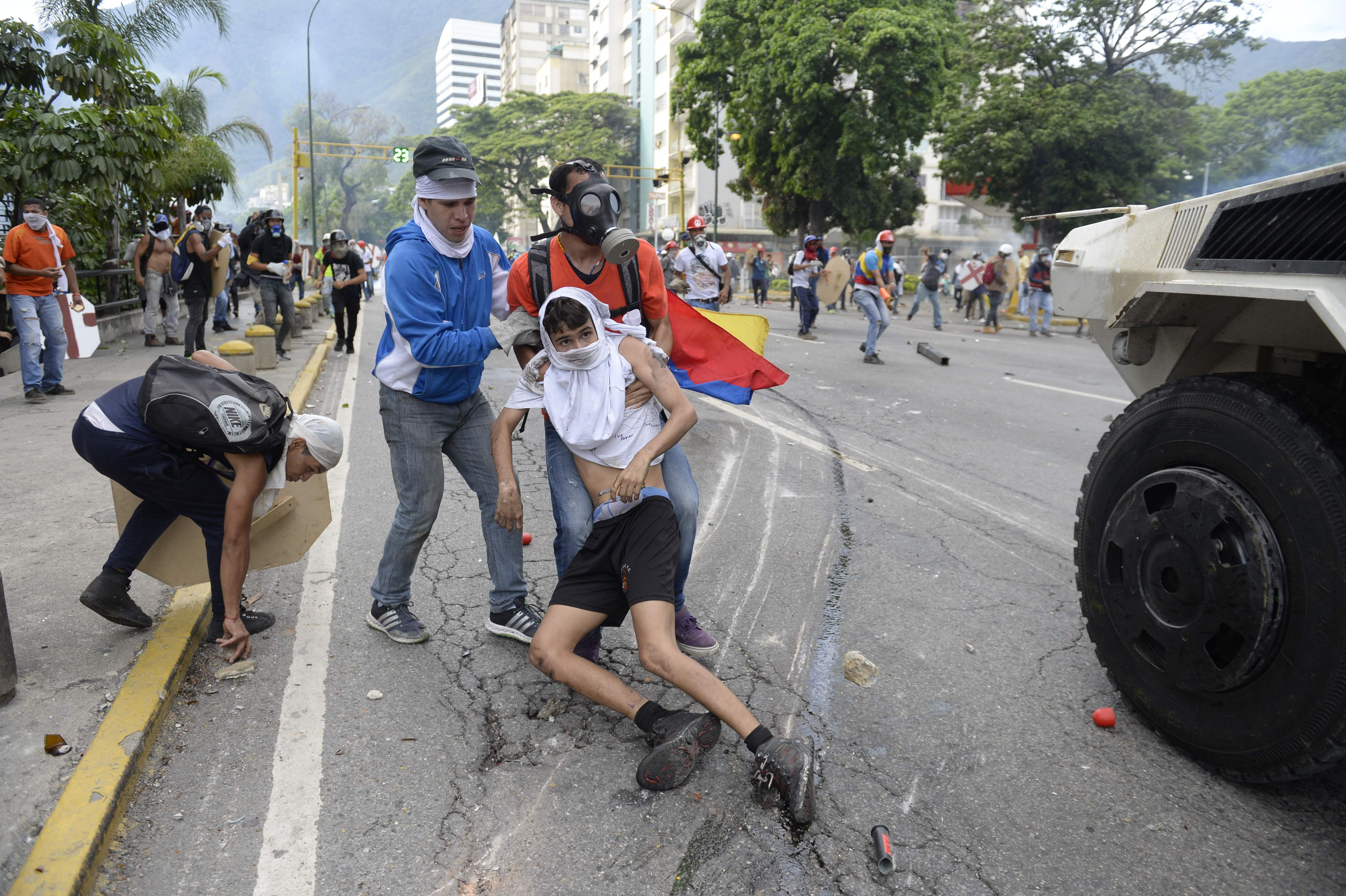 TOPSHOT - An opposition demonstrator ran over by a National Guard control vehicle is dragged away by a fellow demonstrator during a protest against Venezuelan President Nicolas Maduro, in Caracas on May 3, 2017. Venezuela's angry opposition rallied Wednesday vowing huge street protests against President Nicolas Maduro's plan to rewrite the constitution and accusing him of dodging elections to cling to power despite deadly unrest. / AFP PHOTO / FEDERICO PARRA / GRAPHIC CONTENT / TT / kod 444