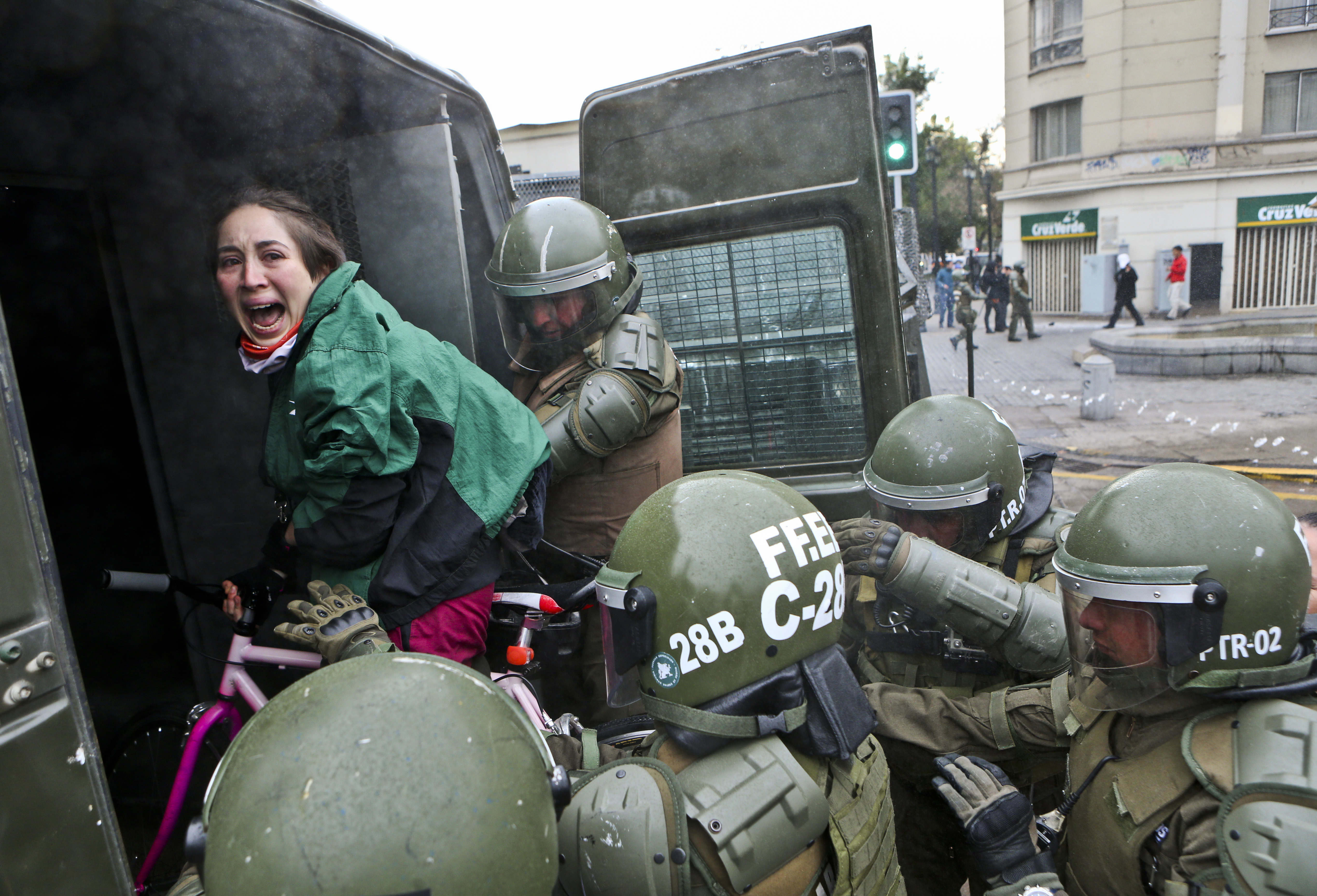 A woman, while on her bicycle, is lifted and placed by police into a paddy wagon during a protest march demanding the government overhaul the education funding system that would include canceling their student loan debt, in Santiago, Chile, Wednesday, June 21, 2017. (AP Photo/Esteban Felix)