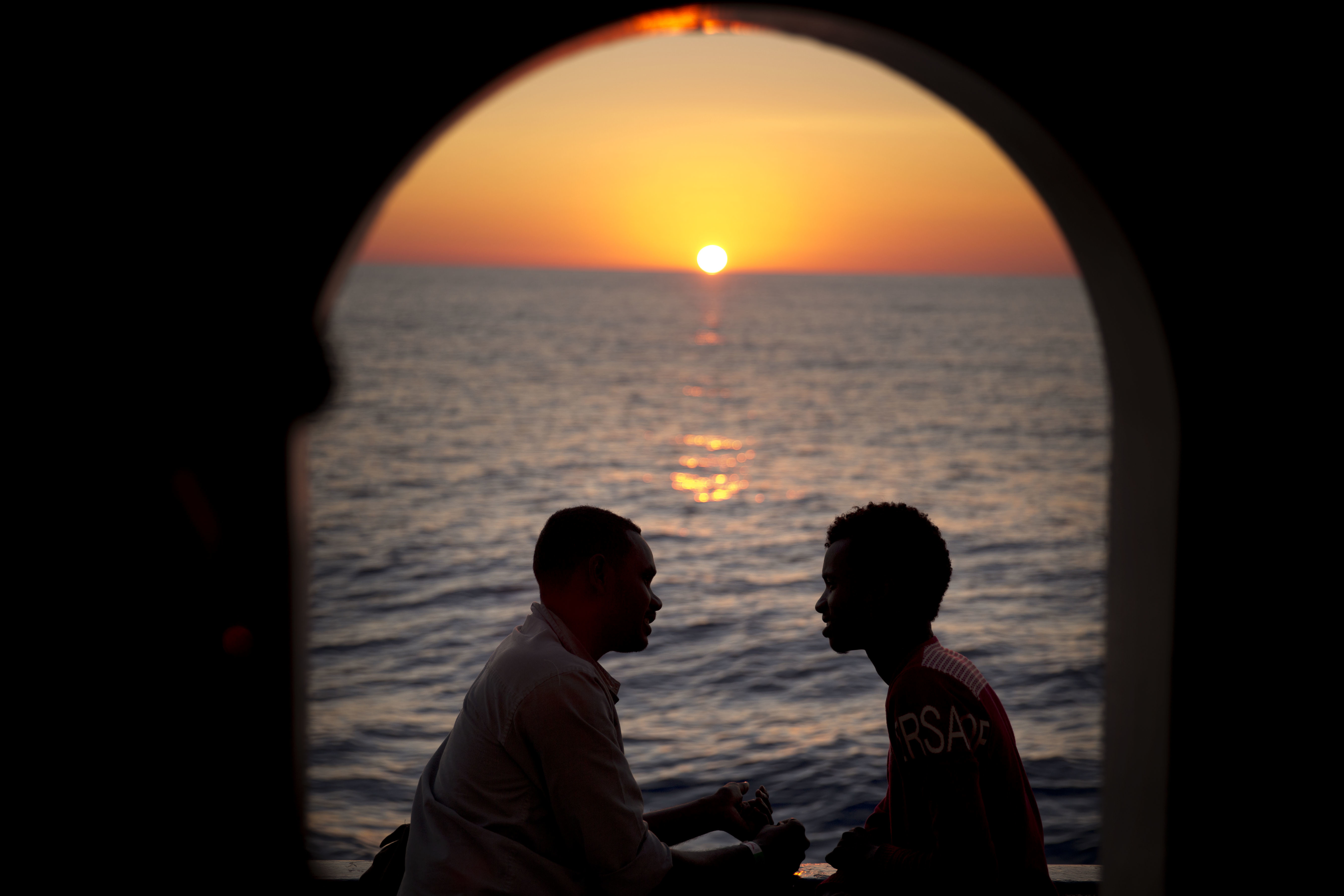 Two men from Sudan talk on the deck of the Golfo Azzurro rescue vessel, after being rescued from a rubber boat out of control near the Libyan coast, on Thursday, June 22, 2017. (AP Photo/Emilio Morenatti)