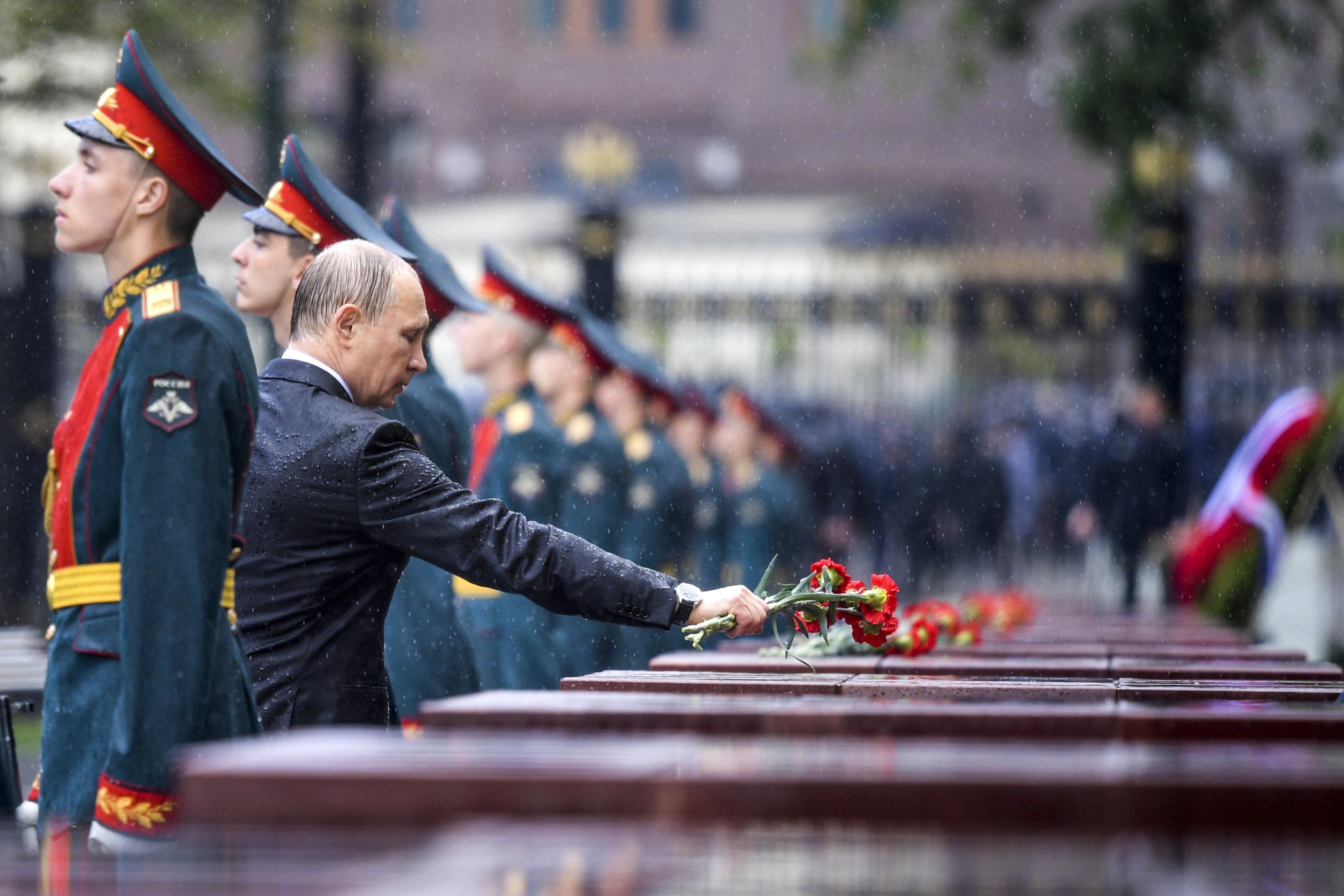 Russian President Vladimir Putin, second left, places flowers at a monument to cities-heroes as he takes part in a wreath laying ceremony to the Tomb of Unknown Soldier in pouring rain, in Moscow, Russia, Thursday, June 22, 2017, marking the 76th anniversary of the Nazi invasion of the Soviet Union. (Alexei Druzhinin/Sputnik, Kremlin Pool Photo via AP)