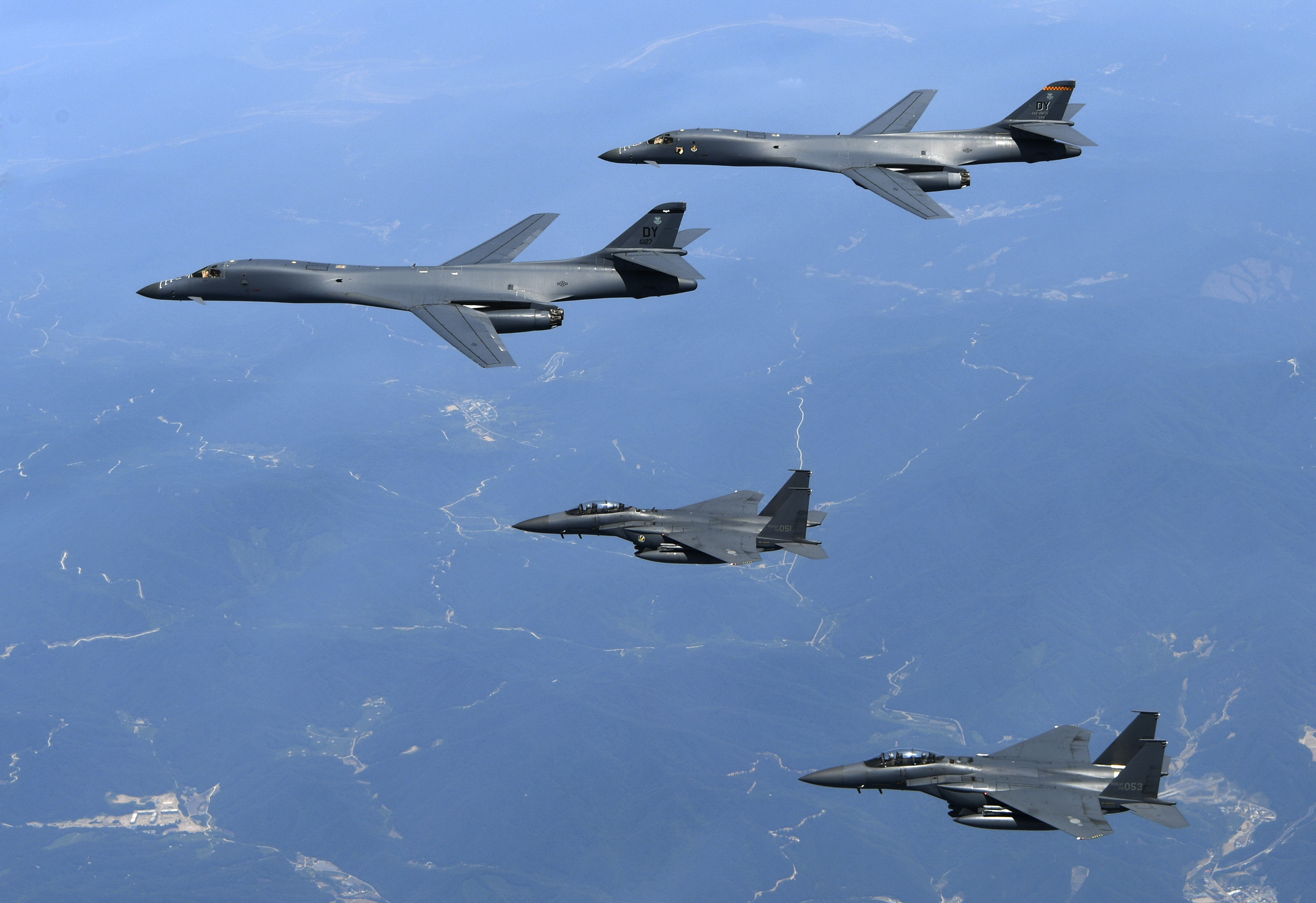 In this Tuesday, June 20, 2017 photo provided by South Korean Defense Ministry, U.S. Air Force B-1B bombers, top, and second from top, and South Korean fighter jets F-15K fly over the Korean Peninsula, South Korea. The United States flew two supersonic bombers over the Korean Peninsula on Tuesday in a show of force against North Korea, South Korean officials said. (South Korean Defense Ministry via AP)
