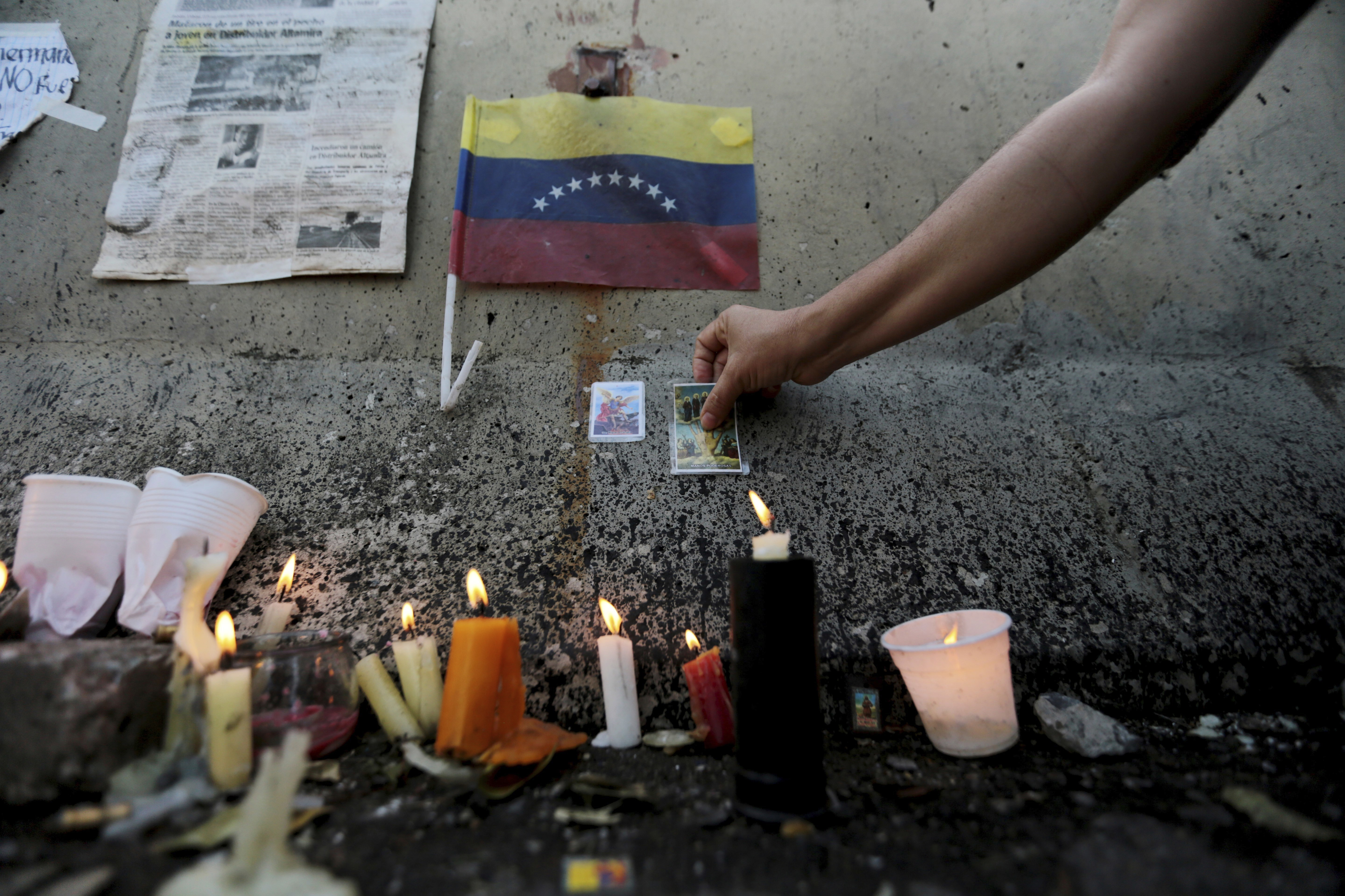 A woman adds a Powerful Hand prayer card to the makeshift memorial created on the spot a student was killed during clashes between anti-government protesters and Bolivarian National Guard officers, during a vigil in Caracas, Venezuela, Wednesday, June 21, 2017. The 17-year-old student was shot dead on Monday the Public Prosecutor's Office said, bringing the death toll to 72 in two months of demonstrations against Venezuelan President Nicolas Maduro. (AP Photo/Fernando Llano)