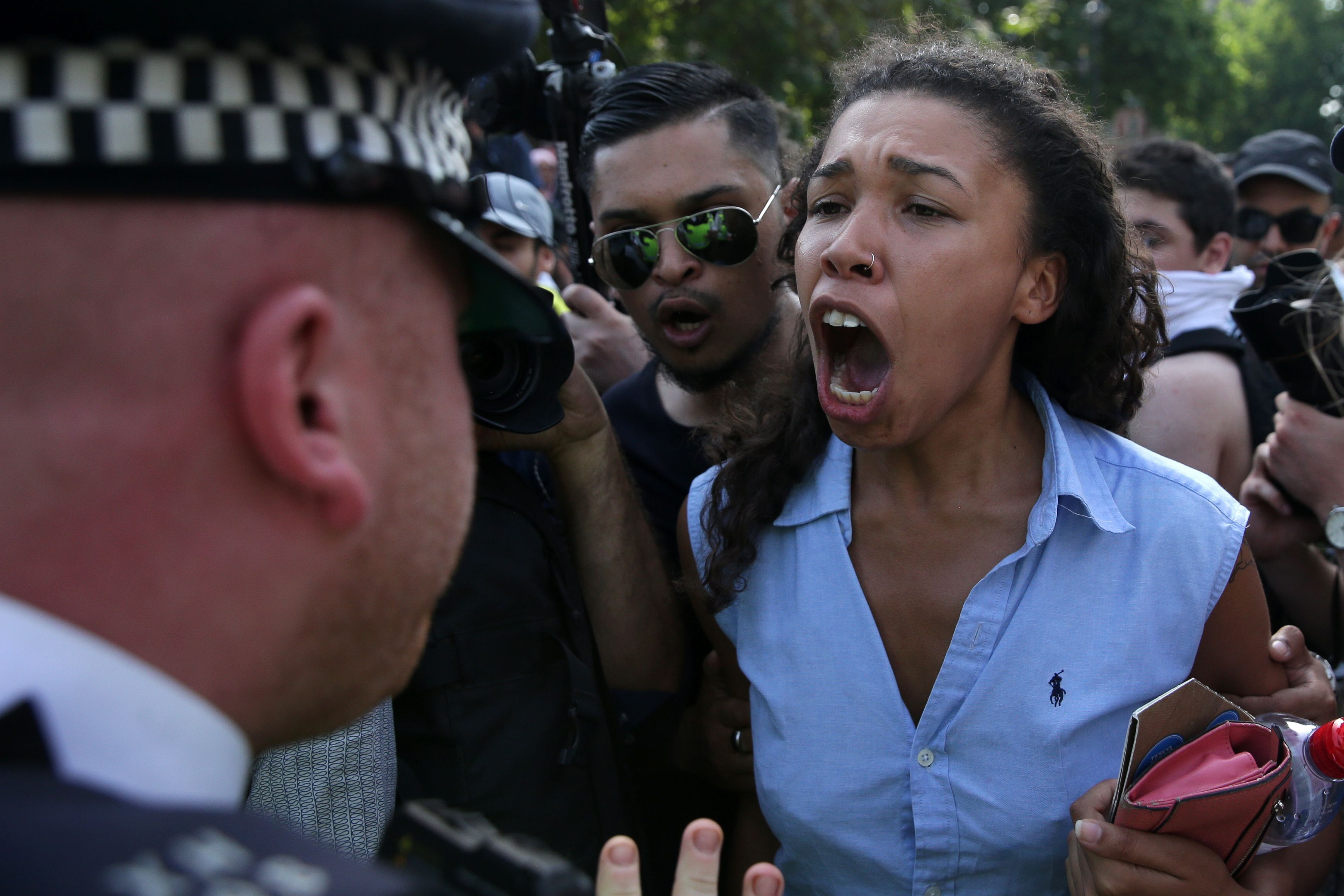 TOPSHOT - A woman clashes with a police officer as protesters gather in central London on June 21, 2017, during an anti-government protest to coincide with the State Opening of Parliament and following the deadly fire at Grenfell Tower. Anti-government protesters highlighting issues including the Grenfell Tower fire marched on parliament from west London after Queen Elizabeth II formally opened parliament and announced the British government's legislative programme two days later than planned. / AFP PHOTO / Daniel LEAL-OLIVAS / TT / kod 444
