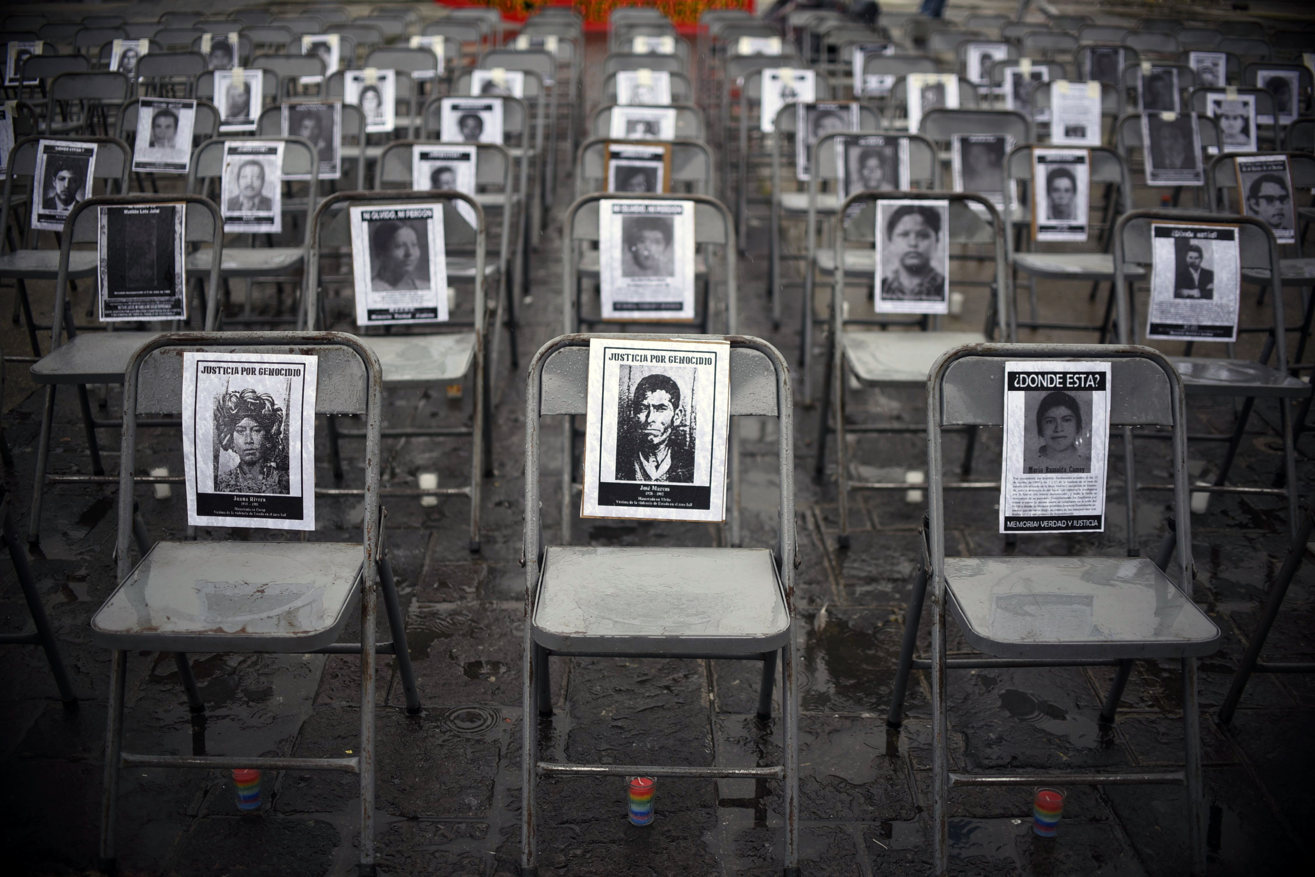 TOPSHOT - Portraits of victims of forced disappearance hang on empty chairs during the ceremony to commemorate the National Day of the Victims of Enforced Disappearances at Constitution Square in Guatemala City on June 21, 2017. / AFP PHOTO / JOHAN ORDONEZ / TT / kod 444