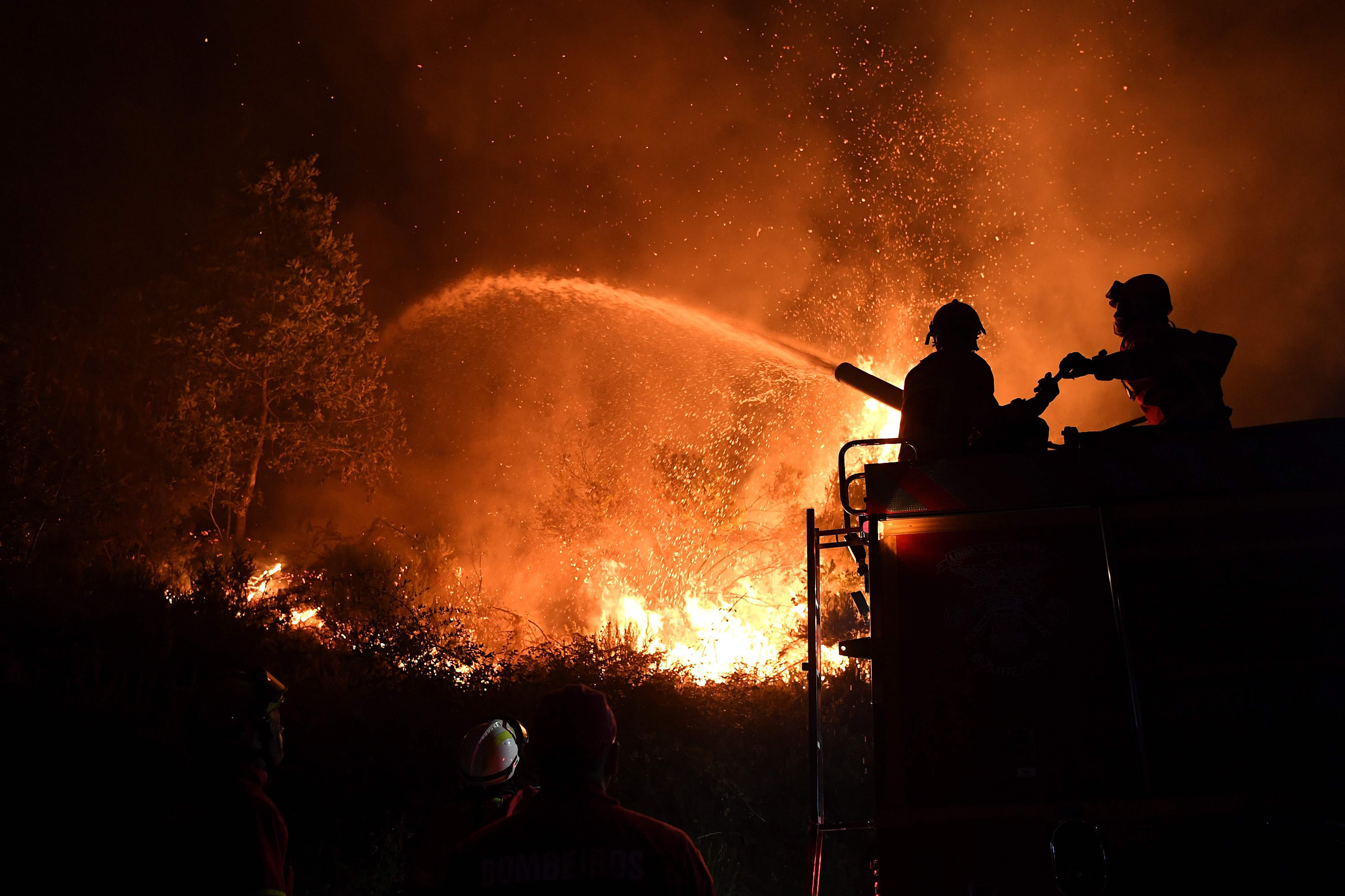 TOPSHOT - Firefighters try to extinguish a wildfire in Colmeal, near Gois on the night of June 21, 2017. The huge forest fire that erupted on June 17, 2017 in central Portugal killed at least 64 people and injured 135 more, with many trapped in their cars by the flames. / AFP PHOTO / FRANCISCO LEONG / TT / kod 444