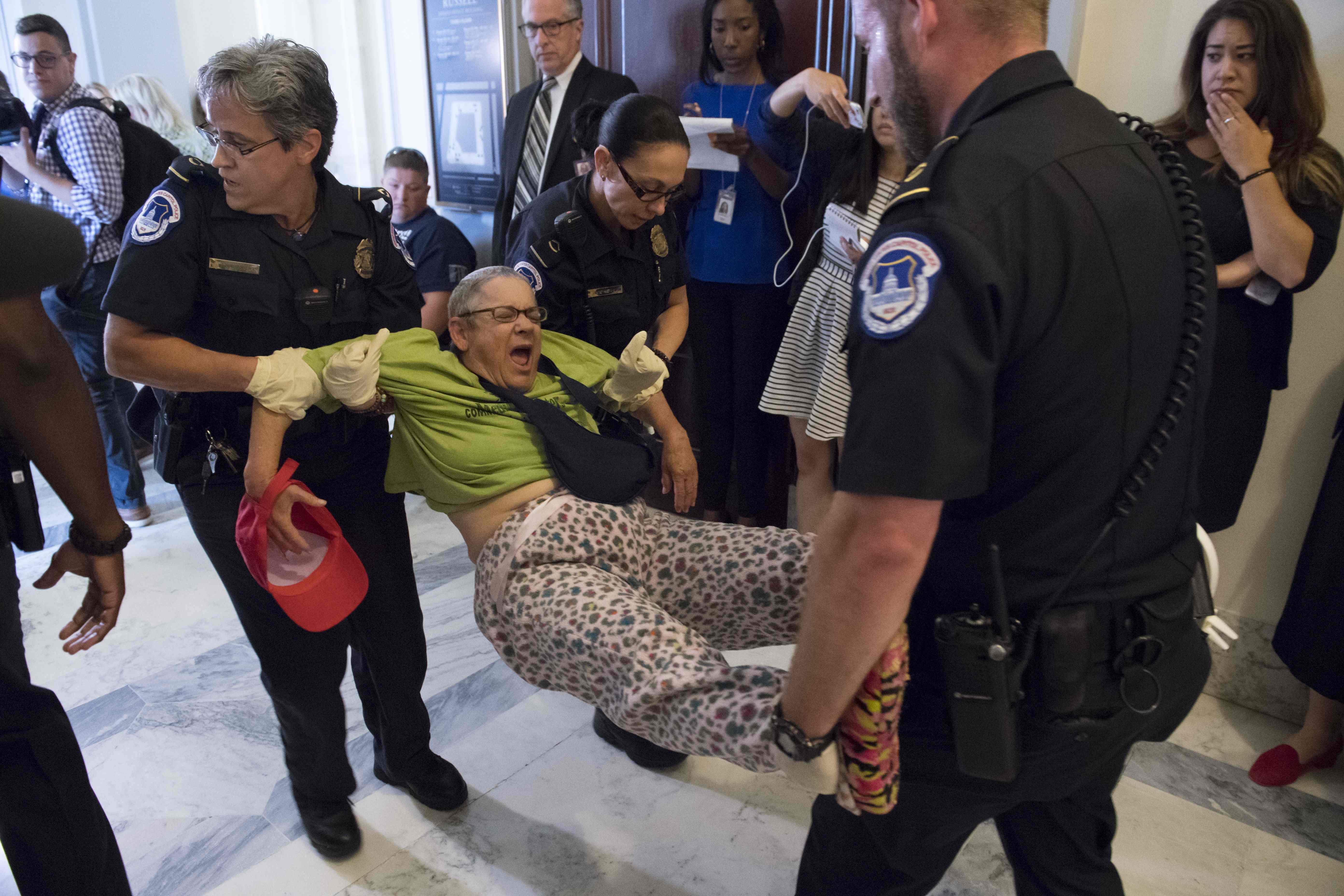 Polisen i Washington arresterar en person som demonstrerar mot ett nytt lagfröslag om sjukvårdsförsäkning i USA. AFP PHOTO / SAUL LOEB / TT /