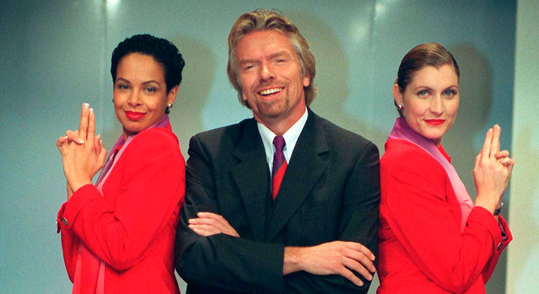 Sir Richard Branson omgiven av två flygvärdinnor från det egna flygbolaget Virgin Atlantic.