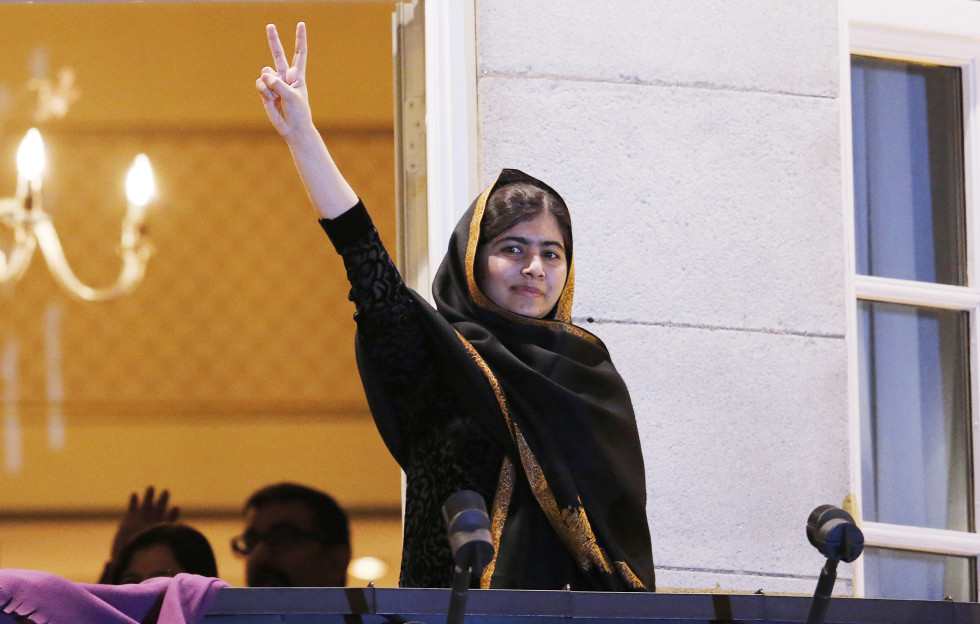 Nobel Peace Prize laureate Malala Yousafzai flashes the 'V' sign from the balcony of the Grand Hotel in Oslo