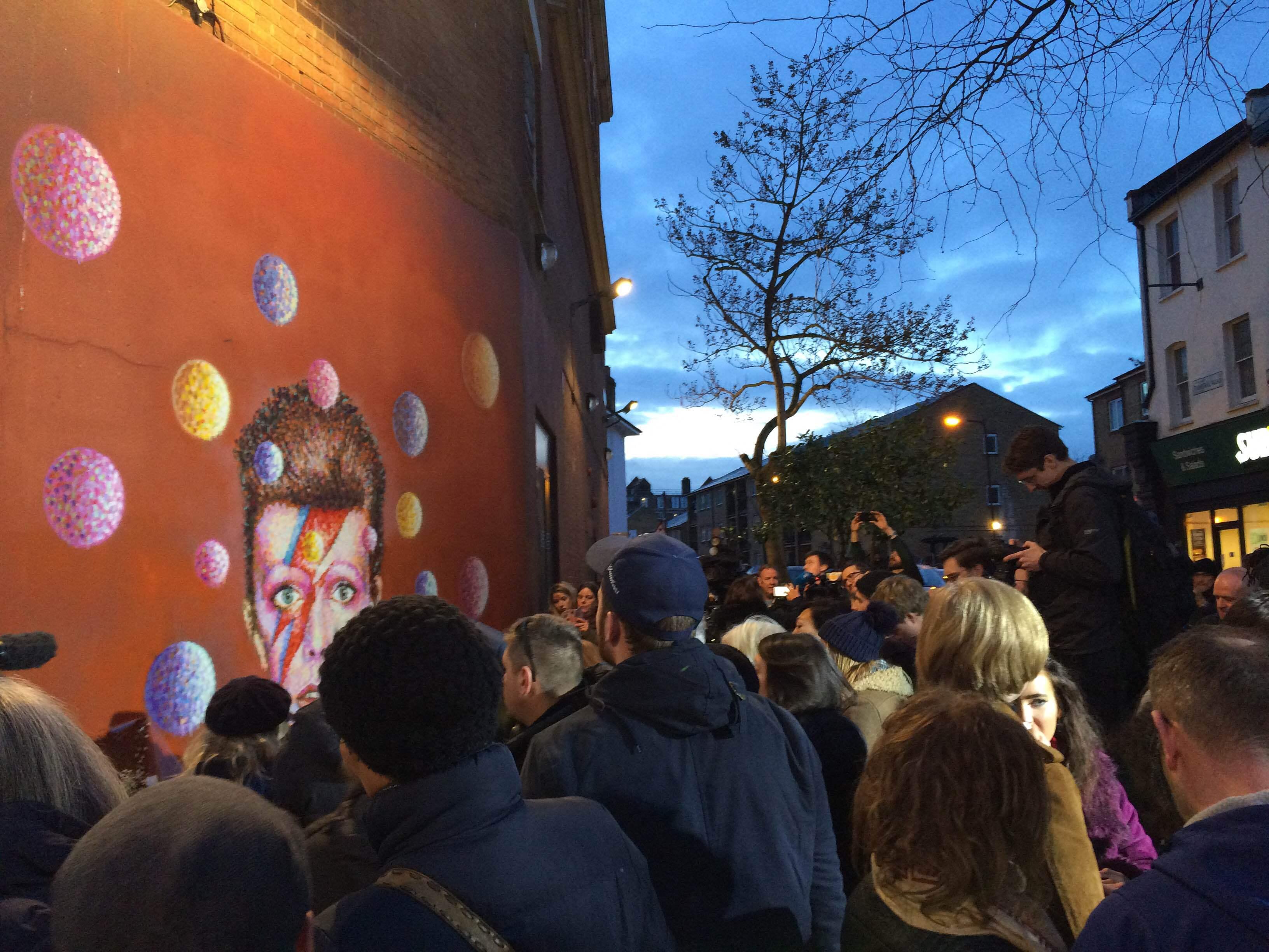 Stor trängsel kring väggmålningen av Bowie.