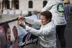 Hannes Hervieu, ordförande för Centerstudenter och riksdagskandidat sätter upp nedrivna affischer. FOTO: Natanael Johansson