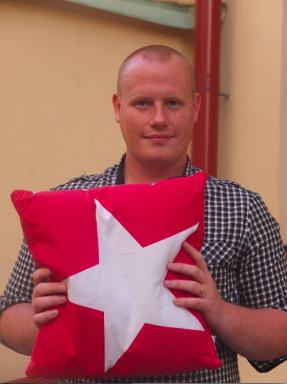 Stefan Lindborg, förbundsordförande Ung Vänster, med kudden som ska skickas till MUF:s ordförande Erik Bengtzboe. FOTO: Pressbild