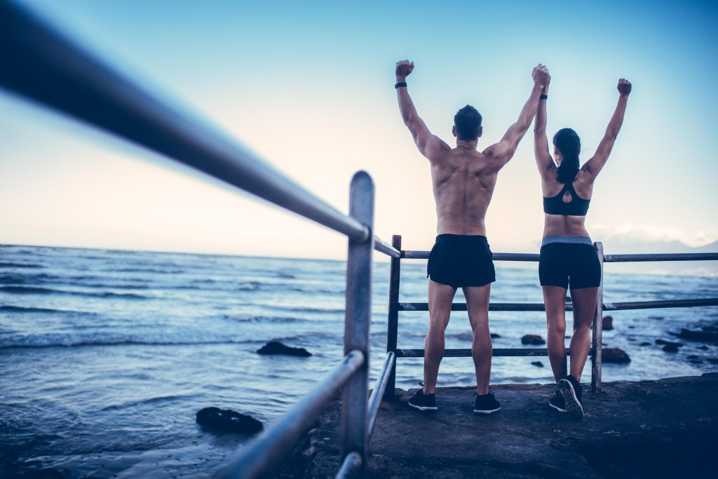 Young adult caucasian couple doing conquer pose after run on the beach