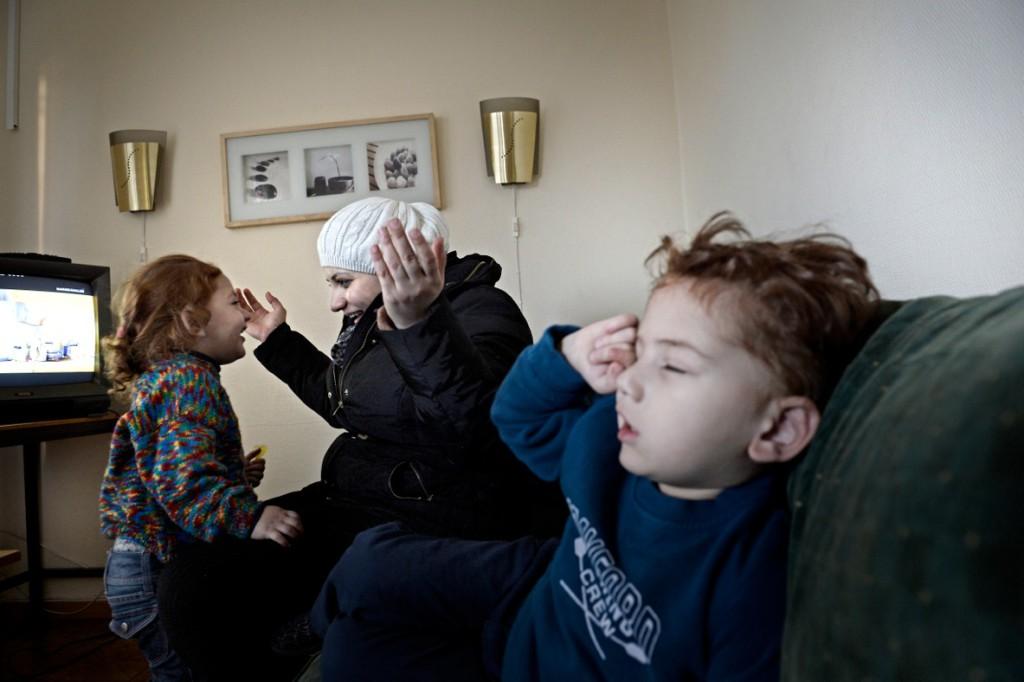 Dima Alkurdi busar med dottern Hala. Bredvid sitter sonen Yazeh, 3, med feber. Foto: Stefan Mattsson.
