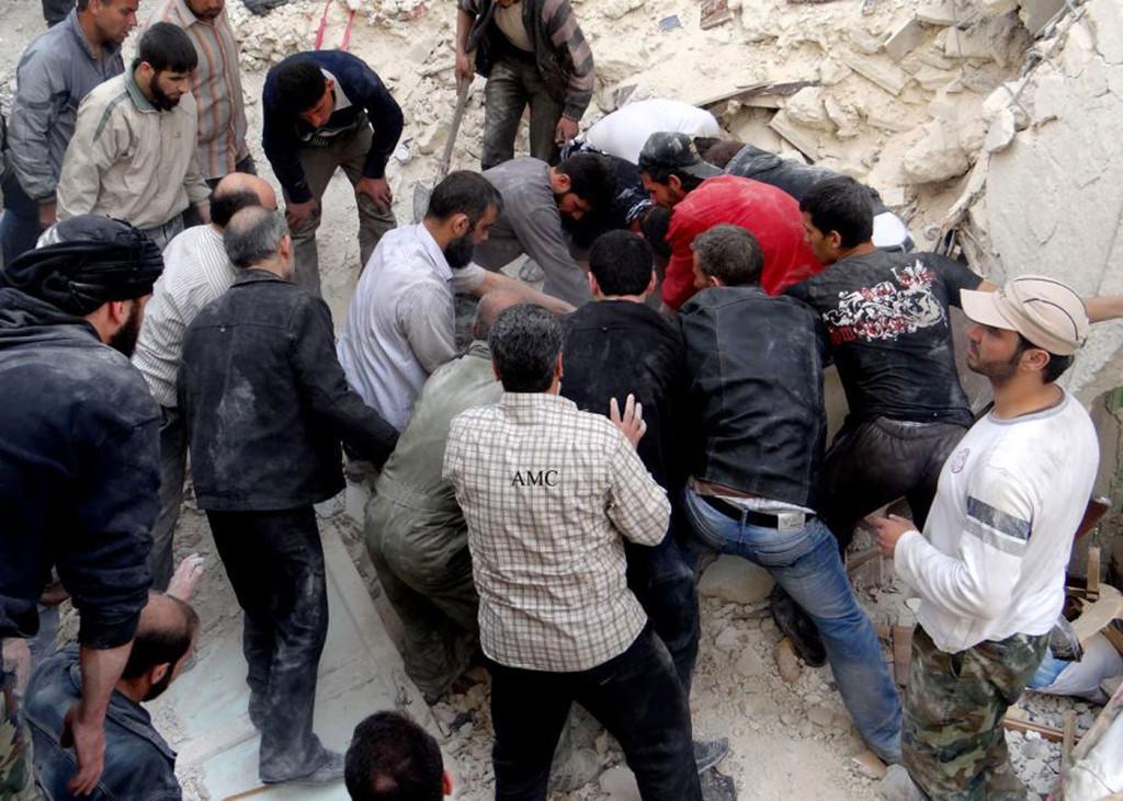 Invånare i staden Aleppo försöker gräva fram begravda människor efter en bombattack. Foto: AP