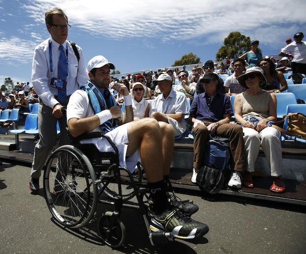 Brian Baker förs ut från banan i rullstol. FOTO: AP