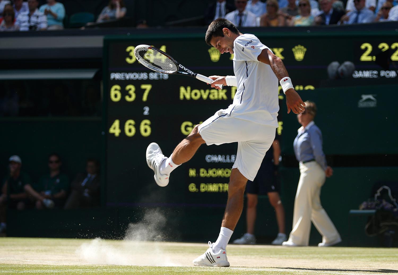 Novak Djokovic tar ut sin frustration på den anrika banan i Wimbledon. FOTO: AP