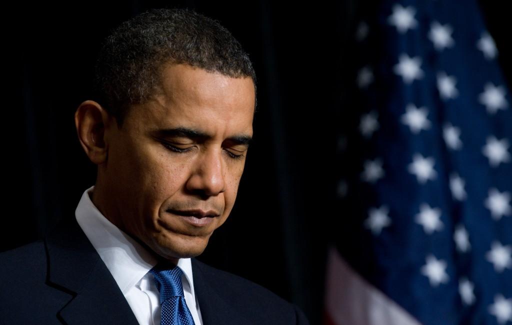 US President Barack Obama bows his head